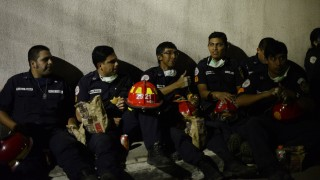 Municipal firemen rest in Santa Catarina Pinula municipality, some 15 km east of Guatemala City, on October 2, 2015. At least 30 people were dead and several hundred missing a day after a devastating landslide hit an area on the outskirts of the Guatemalan capital, officials said. AFP PHOTO/ JOHAN ORDONEZ