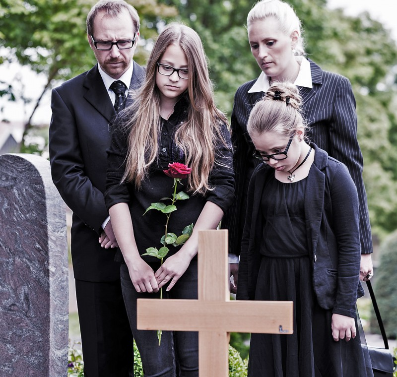 Family mourning at grave on cemetery