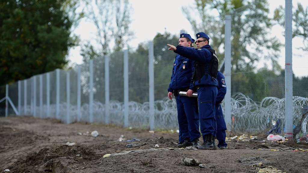 "Police officers patrol along a new border fence at the Hungarian-Croatian border near Zakany on October 17, 2015. The border between Hungary and Croatia has been closed to ""illegal"" migrants, the Hungarian government said, with barbed wire fences being set up to seal the frontier. Croatia announced that it would divert migrants to Slovenia after Hungary said it would close the border with its fellow EU member -- a major transit point for tens of thousands of refugees. AFP PHOTO / ATTILA KISBENEDEK"