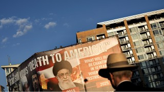 A man walks past a billboard lobbying against an agreement with Iran over its nuclear program September 17, 2015 in Washington, DC.  Iran's foreign minister said last week that Washington must honour a nuclear deal between Tehran and major powers once implementation begins and block any attempt by lawmakers to meddle with it. AFP PHOTO/BRENDAN SMIALOWSKI