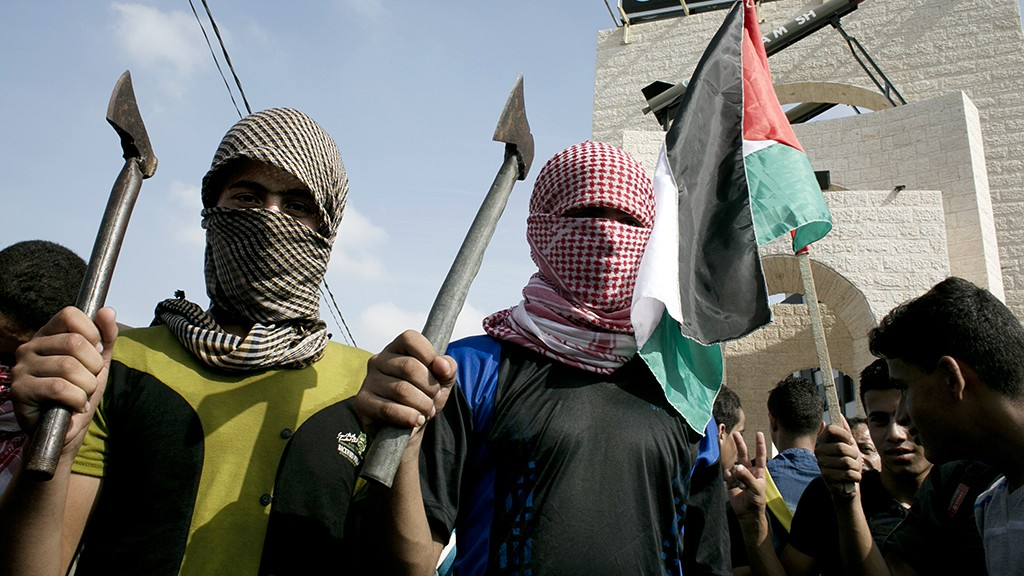 Palestinian students cover their faces with the trademark chequerred keffiyeh and hold up axes as a fellow protester waves a national flag (R) during an anti-Israel protest in the southern Gaza Strip town of Rafah on October 13, 2015, following a wave of stabbings that has hit Israel, Jerusalem and the West Bank  along with violent protests in annexed east Jerusalem and the occupied West Bank, leading to warnings that a full-scale Palestinian uprising, or third intifada, could erupt. The unrest has also spread to the Gaza Strip, with clashes along the border in recent days leaving nine Palestinians dead from Israeli fire. AFP PHOTO / SAID KHATIB