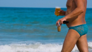 man walking on beach with beer and coffee