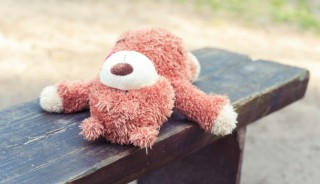 Abandoned on the wooden bench lonely teddy bear toy