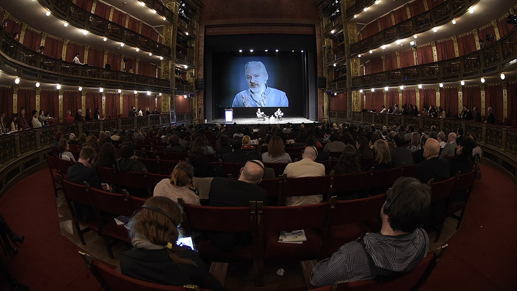 Wikileaks founder Julian Assange (on then screen) takes part in a teleconference during the 2nd International Congress on Universal Jurisdiction in Buenos Aires on September 9, 2015. AFP PHOTO / JUAN MABROMATA