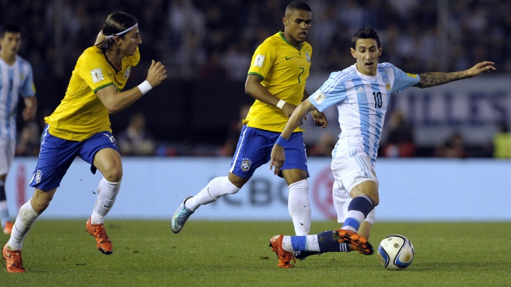 Argentina's Angel Di Maria (R) controls the ball next to Brazil's Filipe Luis (L) and Brazil's Douglas Costa during their Russia 2018 FIFA World Cup South American Qualifiers football match, in Buenos Aires, on November 13, 2015.  AFP PHOTO / ALEJANDRO PAGNI