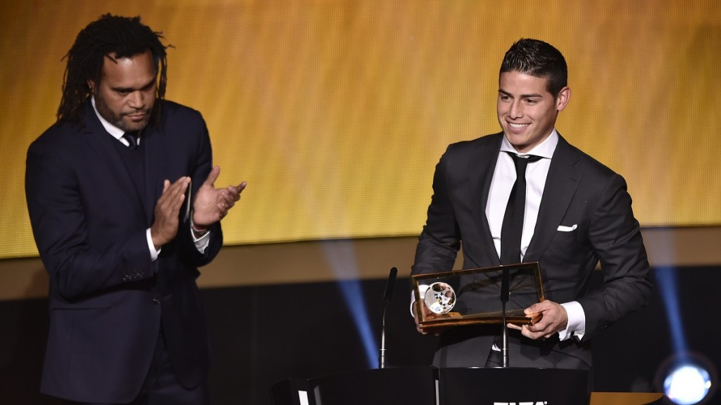 Colombia's midfiedler James Rodriguez (R) speaks after receiving from  French former football player Christian Karembeu (L) the 2014 FIFA Puskas Award for best goal during the FIFA Ballon d'Or award ceremony at the Kongresshaus in Zurich on January 12, 2015.  AFP PHOTO / FABRICE COFFRINI