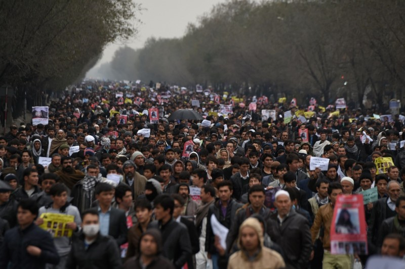 Afghan protesters march during a demonstration, over the killing of seven Shiite Hazaras, in Kabul on November 11, 2015. Thousands of protesters marched coffins containing the decapitated bodies of seven Shiite Hazaras through the Afghan capital Kabul on November 11 to demand justice for the gruesome beheadings, which prompted fears of sectarian bloodshed in the war-torn country. Demonstrators gathered in the rain in west Kabul and marched towards the city centre, chanting death slogans to the Taliban and the Islamic State group while demanding justice and protection from the government. AFP PHOTO / SHAH Marai