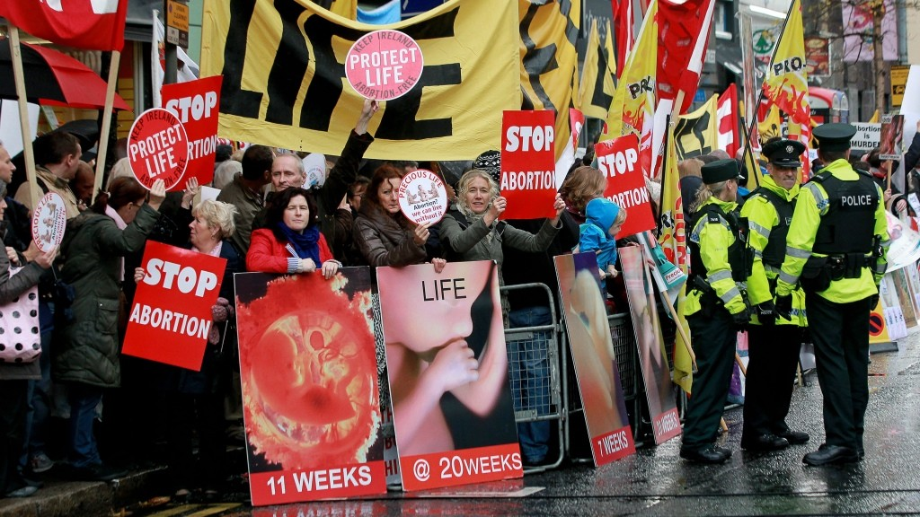 """Police walk around abortion protestors holding up placards outside the Marie Stopes clinic, the first private clinic to offer abortions to women in Belfast, Northern Ireland on October 18, 2012. Dozens of pro-life campaigners protested outside the first abortion clinic in Northern Ireland as it opened to the public. Around 50 protesters brandishing placards saying """"Life is precious"""" and showing photographs of foetuses gathered outside the privately run clinic in an anonymous building in Belfast. AFP PHOTO/ Peter Muhly / AFP / PETER MUHLY"""