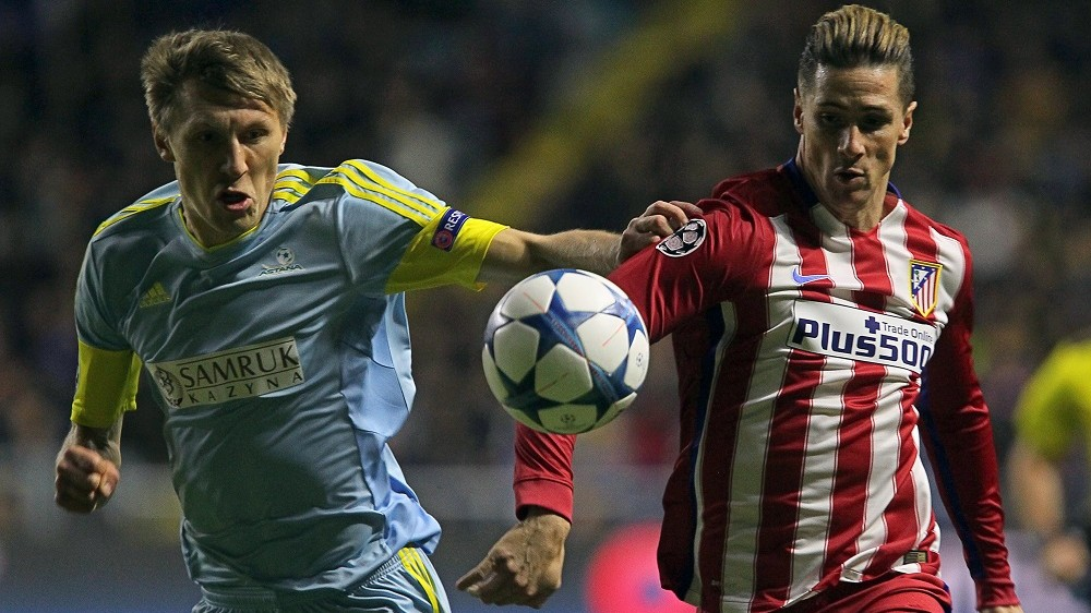 Astana's Kazakh defender Evgeni Postnikov (L) vies for the ball with Atletico Madrid's forward Fernando Torres during the UEFA Champions League group C football match between FC Astana and Club Atletico de Madrid at the Astana Arena stadium in Astana on November 3, 2015. AFP PHOTO / STANISLAV FILIPPOV