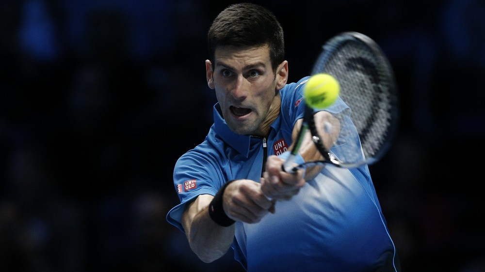 Serbia's Novak Djokovic returns against Japan's Kei Nishikori during their men's singles group stage match on day one of the ATP World Tour Finals tennis tournament in London on November 15, 2015.  AFP PHOTO / ADRIAN DENNIS