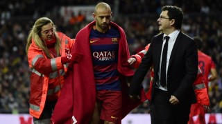 """Barcelona's Argentinian defender Javier Mascherano (C) walks with a blanket around him assisted by a medic during the Spanish league """"Clasico"""" football match Real Madrid CF vs FC Barcelona at the Santiago Bernabeu stadium in Madrid on November 21, 2014.   AFP PHOTO / PIERRE-PHILIPPE MARCOU / AFP / PIERRE-PHILIPPE MARCOU"""