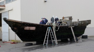 This picture taken on November 24, 2015 shows coast guard officials investigating a wooden boat at the Fukui port in Sakai city in Fukui prefecture, western Japan after the ship was found drifting off the coast of Fukui. Japan is investigating nearly a dozen suspicious boats recently found drifting off the country's coastline, some with decaying bodies aboard, officials said on November 27, as media speculated they came from North Korea. At least 11 cases involving wooden boats -- some badly damaged -- with 20 bodies on board have been reported during October and November.   AFP PHOTO / JIJI PRESS    JAPAN OUT / AFP / JIJI PRESS / JIJI PRESS