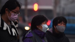 Women wear masks as they cross a road on a polluted day in Beijing on November 27, 2015. China is the world's largest polluter and will be a key player at next week's climate change talks in Paris in the face of disputes over whether developed or developing countries should bear more of the burden for reducing emissions. AFP PHOTO / GREG BAKER / AFP / GREG BAKER