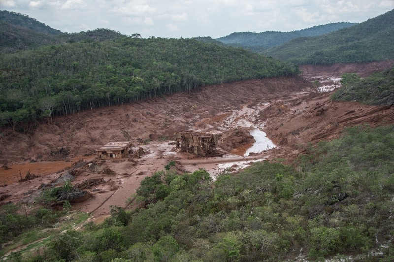 Aerial view of damages after a dam burst in the village of Bento Rodrigues, in Mariana, Minas Gerais state, Brazil on November 6, 2015. A dam burst at a mining waste site unleashing a deluge of thick, red toxic mud that smothered a village killing at least 17 people and injuring some 75. The mining company Samarco, which operates the site, is jointly owned by two mining giants, Vale of Brazil and BHP Billiton of Australia. AFP PHOTO /  CHRISTOPHE SIMON