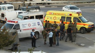 Israeli security forces and emergency personnel gather at the site of a reported car-ramming attack on Israeli border guards at the Beit Einun junction, north of the West Bank city of Hebron, on November 1, 2015. Earlier in the day, a Palestinian tried to stab an Israeli soldier and was shot dead in the same area, the Israeli army said. AFP PHOTO / HAZEM BADER