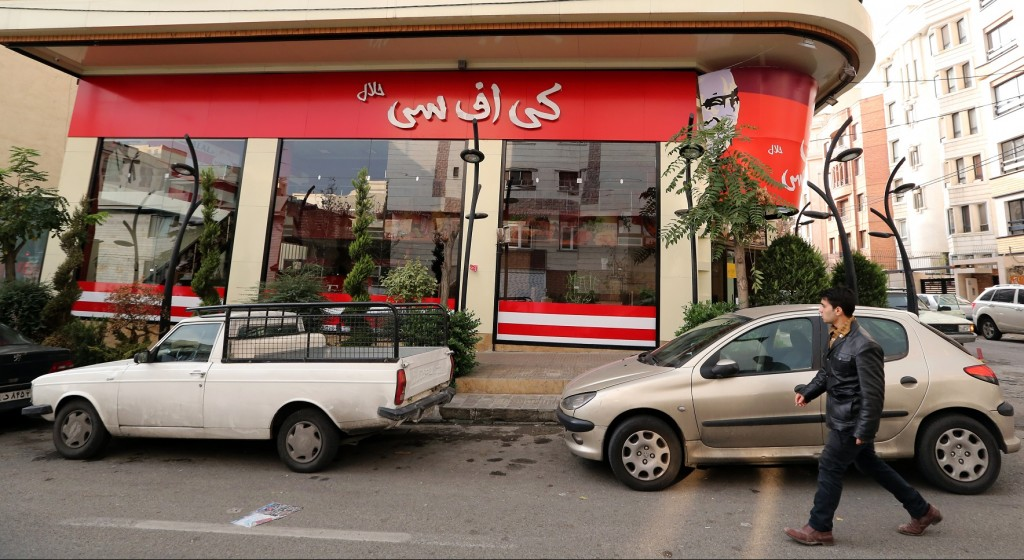 """A man walks past the fried chicken shop """"KFC Halal"""", using the brand name of US fast food giant KFC, after it was closed by Iranian police, on November 3, 2015, in the capital Tehran. """"Police closed the 'KFC' restaurant as it didn't have authorisation and had been operating under a false license,"""" reported the news site of Iran's Young Journalist Club, which is affiliated with state television. AFP PHOTO / STR"""