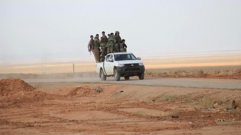 """Syrian pro-government forces ride on a pickup truck on the only road into the government-held side of Aleppo after they reported recaptured it from Islamic State group fighters, on Novembre 4, 2015. The army gained full control of the route from the regime-controlled west of Aleppo to Khanasser, Ithriya and Al-Salmiyeh """"after eliminating a number of Daesh (IS) terrorists,"""" Syrian state television said.  AFP PHOTO / GEORGE OURFALIAN"""