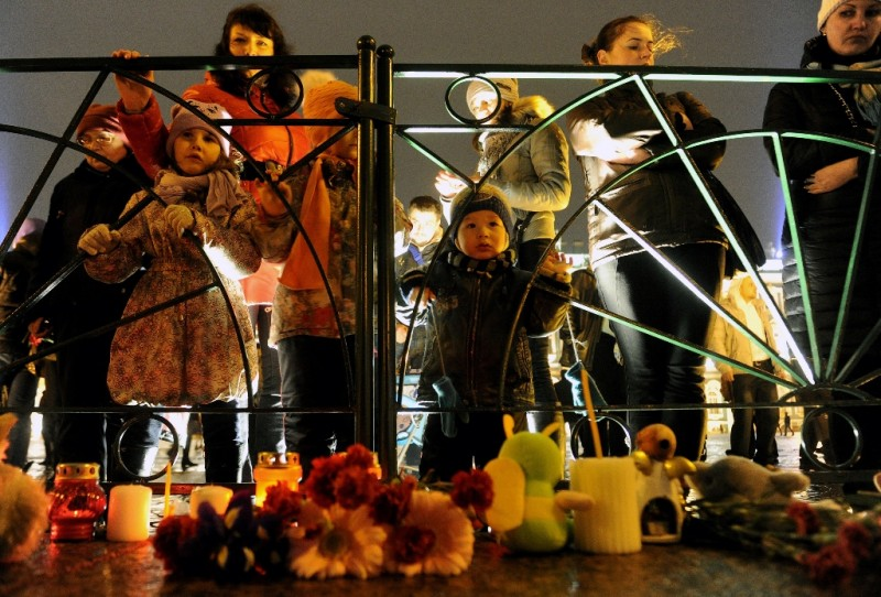 People stand in front of candles and flowers in central Saint Petersburg on November 1, 2015, in memory of the victims of a jetliner crash. Flags flew at half-mast in Russia on November 1 as the country mourned its worst air disaster after a jetliner full of Russian tourists crashed in Egypt, killing all 224 on board. AFP PHOTO / OLGA MALTSEVA