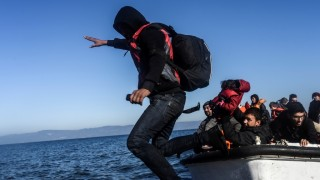 A man jumps off a boat as migrants and refugees arrive on the Greek island of Lesbos after crossing the Aegean Sea from Turkey on November 13, 2015. EU leaders on November 12 struck an aid-for-cooperation deal with Africa and proposed a summit this year with Turkey in a two-front push with wary partners to tackle an unprecedented migrant crisis. AFP PHOTO / BULENT KILIC
