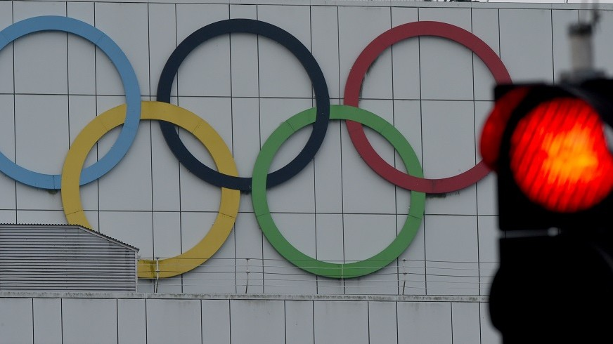 ILLUSTRATION- The red light of a traffic light pictured next to the Olympic rings on a building in Kiel, Germany, 27 November 2015. The results of the referendum on the bid for the 2024 Summer Olympics will be announced on 29 November. If Kiel residents vote yes, the city will move ahead with its bid for the sailing events. Photo: CARSTENREHDER/dpa