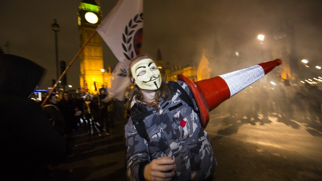 """TOPSHOTS An anti-capitalist protesters wearing a Guy Fawkes mask carries a traffic cone during the """"Million Masks March"""" protest march, organised by the group Anonymous, as it passes Parliament Square in London on November 5, 2015. The protest was held on the night of Britain's Guy Fawkes Night, and many of the marchers wore the white masks of the man who plotted to blow up parliament in 1605, now associated with Anonymous.   AFP PHOTO / JACK TAYLOR"""