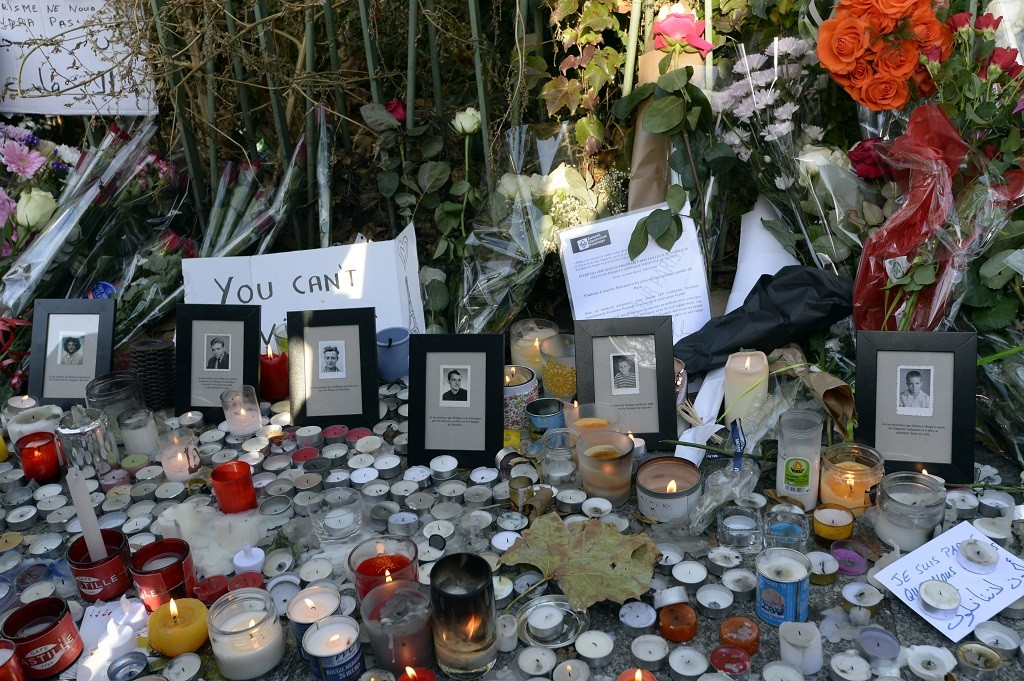 TOPSHOTS Flowers, candles and photos are placed along a police cordon set-up close to the Bataclan concert hall on November 15, 2015 in Paris, following a series of coordinated attacks in and around Paris on November 13. Islamic State jihadists claimed a series of coordinated attacks by gunmen and suicide bombers in Paris that killed at least 129 people and wounded hundreds more in scenes of carnage at a concert hall, restaurants and the national stadium.  AFP PHOTO / MIGUEL MEDINA