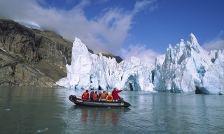 Glacier with tourist expedition in inflatable zodiac, southern Greenland Fjords, Greenland.  Biosphoto / Minden Pictures / Tui De Roy
