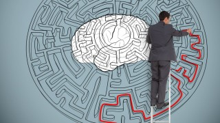Businessman trying to solve a large maze with a brain illustration
