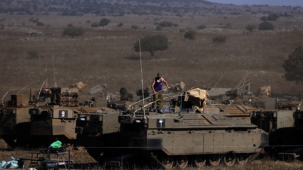 An Israeli soldier stands on top of an armoured personnel carrier stationed in the Israeli-annexed Golan Heights on August 21, 2015, after rockets fired from Syria to northern Israel. Israel launched artillery and air strikes against Syrian army positions in the Golan Heights on August 20 in response to rocket fire, military sources said. AFP PHOTO / AHMAD GHARABLI / AFP / AHMAD GHARABLI