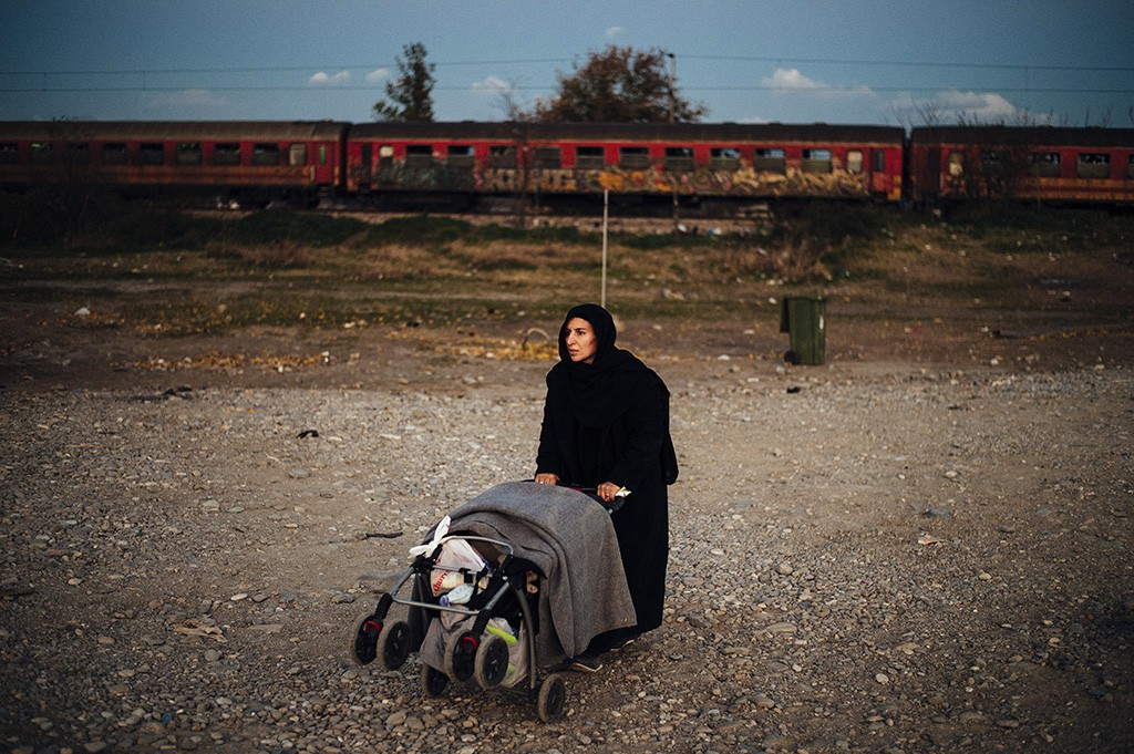 TOPSHOTSA woman pushes a cart as migrants and refugees prepare to board a train heading to Serbia after crossing the Greek-Macedonian border near Gevgelija on November 16, 2015.  European leaders tried to focus on joint action with Africa to tackle the migration crisis, as Slovenia became the latest EU member to act on its own by barricading its border.   AFP PHOTO / DIMITAR DILKOFF