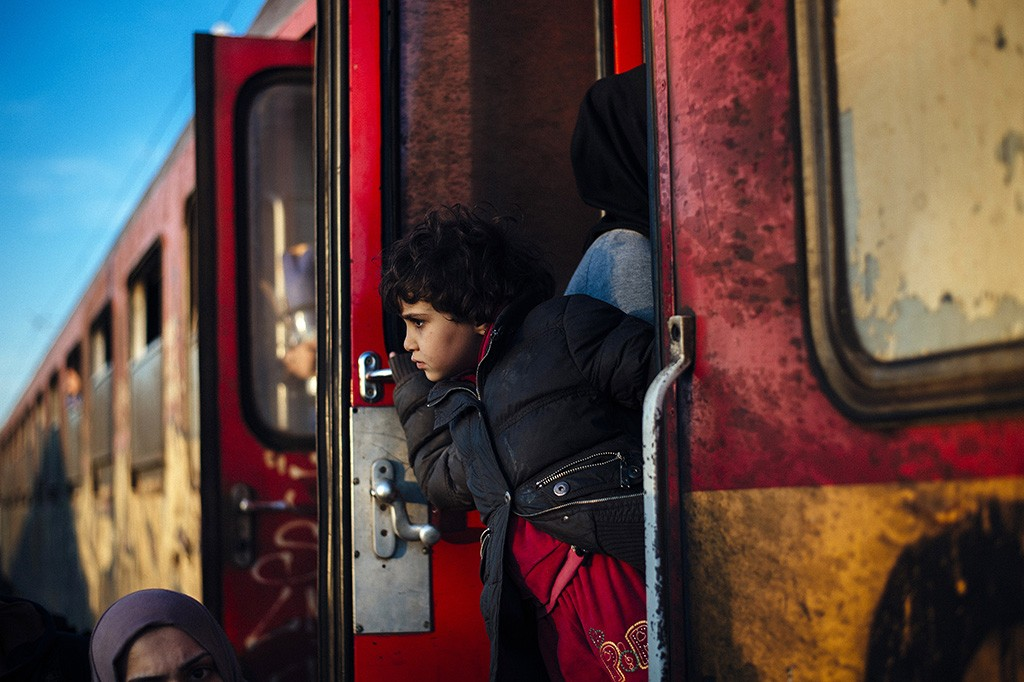 A child looks on as migrants and refugees prepare to board a train heading to Serbia after crossing the Greek-Macedonian border near Gevgelija on November 16, 2015.  European leaders tried to focus on joint action with Africa to tackle the migration crisis, as Slovenia became the latest EU member to act on its own by barricading its border.   AFP PHOTO / DIMITAR DILKOFF