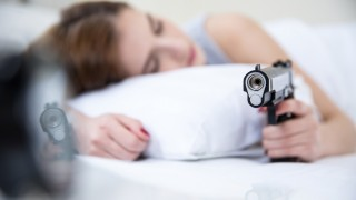 Woman in bed sleeps with hand on gun