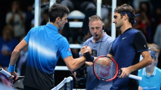 Switzerland's Roger Federer (R) shakes hands with Serbia's Novak Djokovic after winning his men's singles group stage match on day three of the ATP World Tour Finals tennis tournament in London on November 17, 2015. Federer won the match 7-5, 6-2.   AFP PHOTO / GLYN KIRK