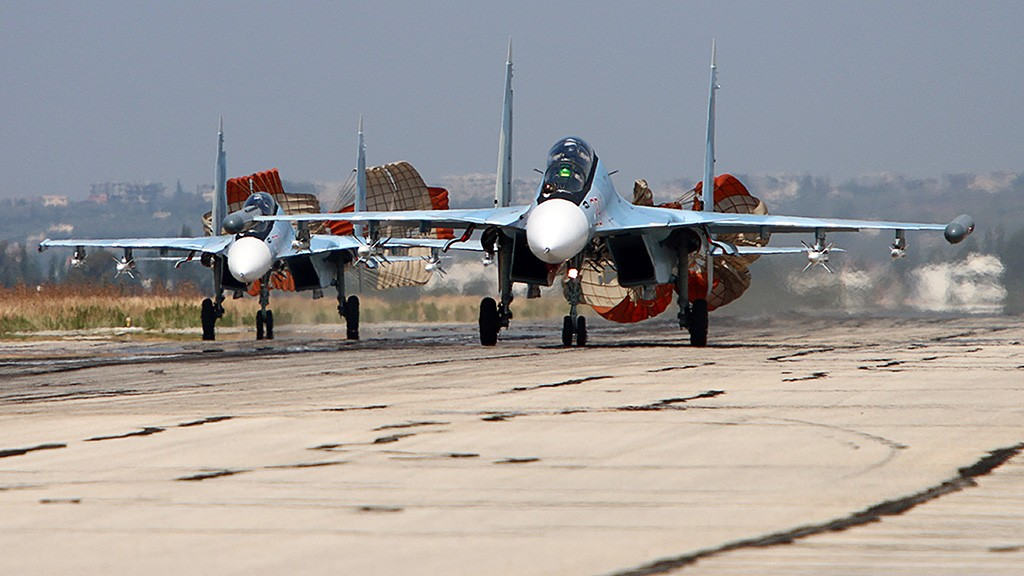 A picture taken on October 3, 2015 shows Russian Sukhoi Su-30 SM jet fighters landing on a runway at the Hmeimim airbase in the Syrian province of Latakia. AFP PHOTO / KOMSOMOLSKAYA PRAVDA / ALEXANDER KOTS*RUSSIA OUT* / AFP / KOMSOMOLSKAYA PRAVDA / ALEXANDER KOTS