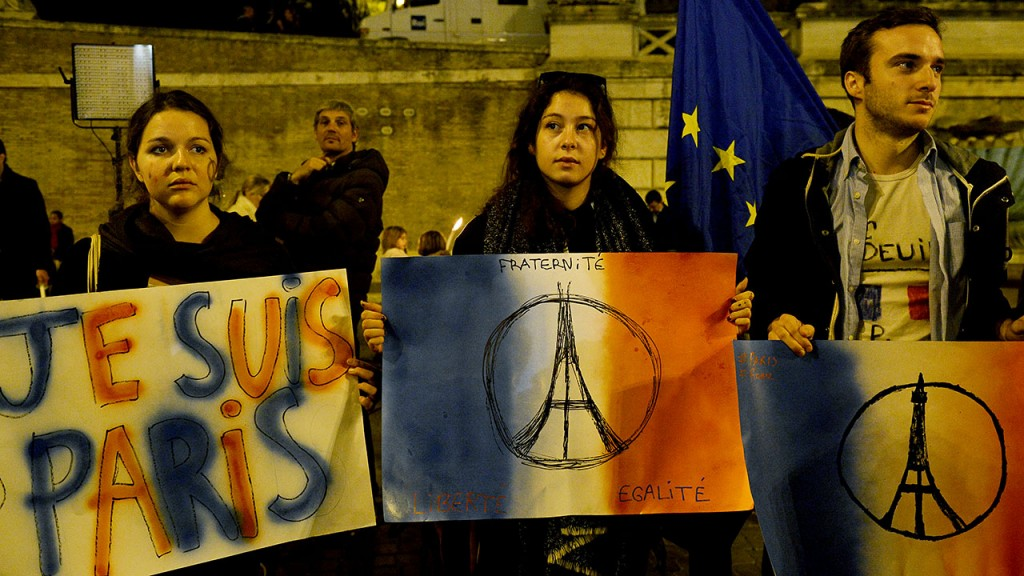 Women hold placards expressing solidarity in the wake of the Paris attacks in the Piazza del Popolo in Rome on on November 14, 2015, during a vigil a day after deadly the attacks in Paris.  Islamic State jihadists claimed a series of coordinated attacks by gunmen and suicide bombers in Paris that killed at least 128 people in scenes of carnage at a concert hall, restaurants and the national stadium.AFP PHOTO / TIZIANA FABI