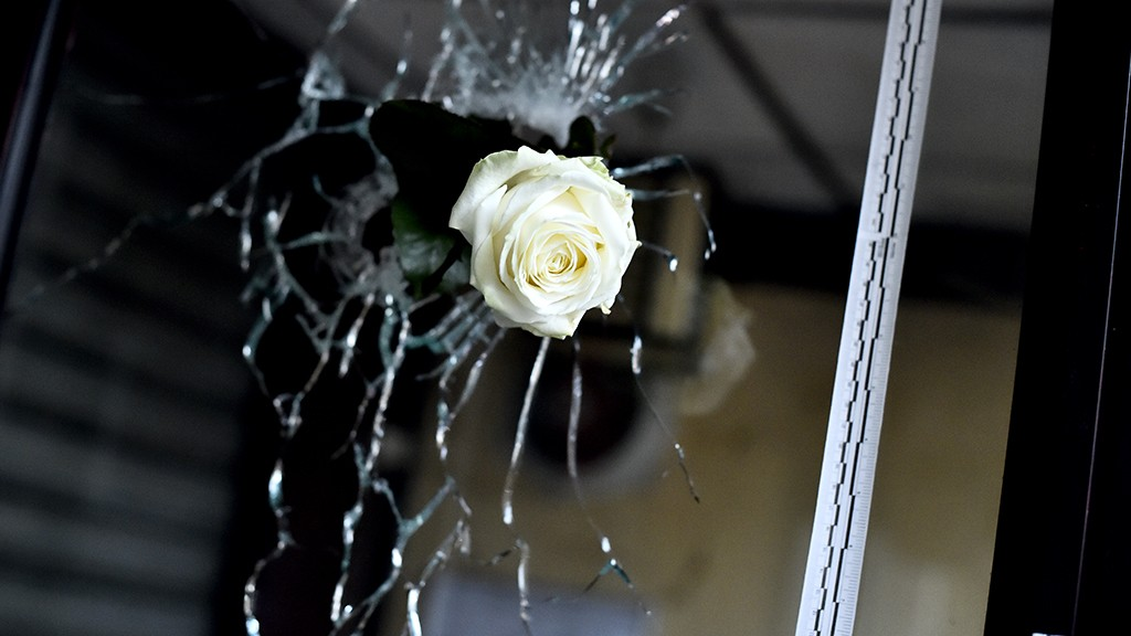 A rose is pictured in a bullet hole in the window of a Japanese restaurant next to the cafe 'La Belle Equipe', Rue de Charonne, in Paris on November 14, 2015, following a series of coordinated attacks in and around Paris late on November 13. At least 128 people were killed in the Paris attacks on the evening of November 13, with 180 people injured, 80 of them seriously, police sources told AFP. AFP PHOTO / LOIC VENANCE