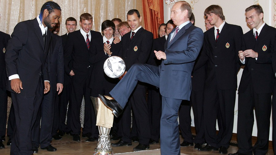Russian President Vladimir Putin plays with a soccer presented him by the winners of UEFA Cup, players of the CSKA Moscow, as player Vagner Silva de Souza (L) and other team members watch 21 May 2005 during a meeting at the Novo-Ogariovo presidential residence outside Moscow. AFP PHOTO / POOL / SERGEI CHIRIKOV (Photo credit should read SERGEI CHIRIKOV/AFP/Getty Images)