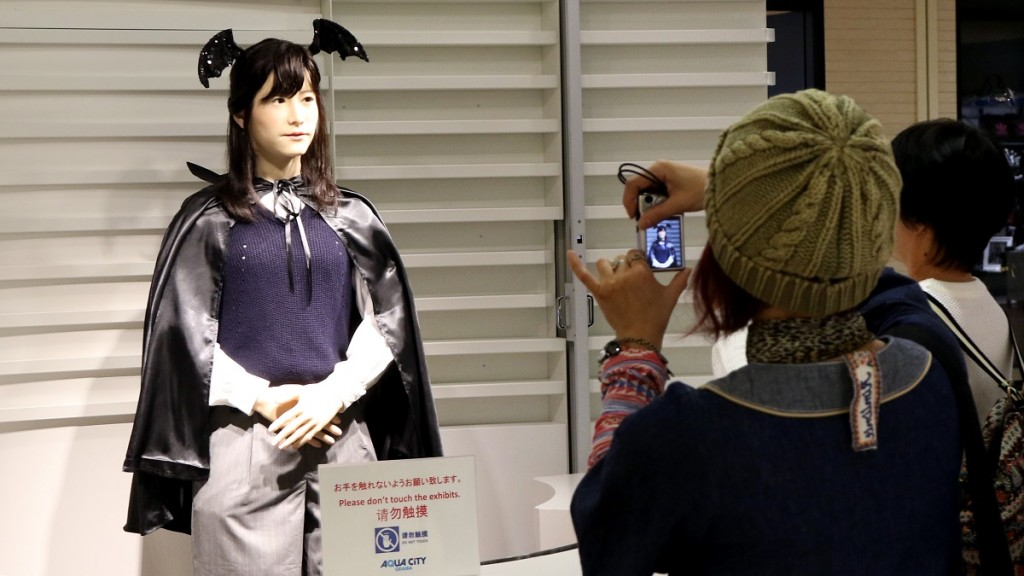 Humanoid robot Chihira Junko (L), clad in a Halloween costume, greets customers at a shopping mall in Tokyo on October 26, 2015.  The android, produced by Japanese electronics giant Toshiba, can give guidance to visitors in Japanese, English and Chinese.  AFP PHOTO / Yoshikazu TSUNO