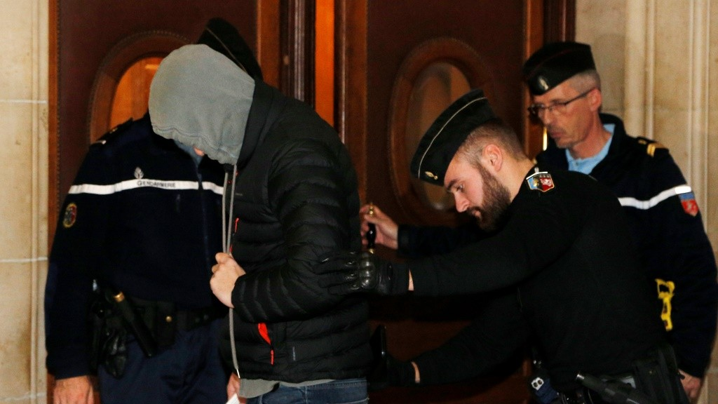 An unnamed defendant arrives hiding his face at Paris courthouse on December 01, 2015 for the opening of the trial of seven men accused of recruiting French jihadists and help them travel to Syria.   The main defendant of the trial, Salim Benghalem, is thought to be fighting in Syria and will be judged in abstentia. / AFP / FRANCOIS GUILLOT
