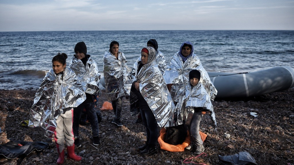 Refugees and migrants arrive in the island of Lesbos after crossing the Aegean sea from Turkey, on December 8, 2015. At least six children died on December 8, 2015 when a boat carrying Afghan migrants sank in Turkish waters while on its way to Greece, local media reported.  / AFP / ARIS MESSINIS
