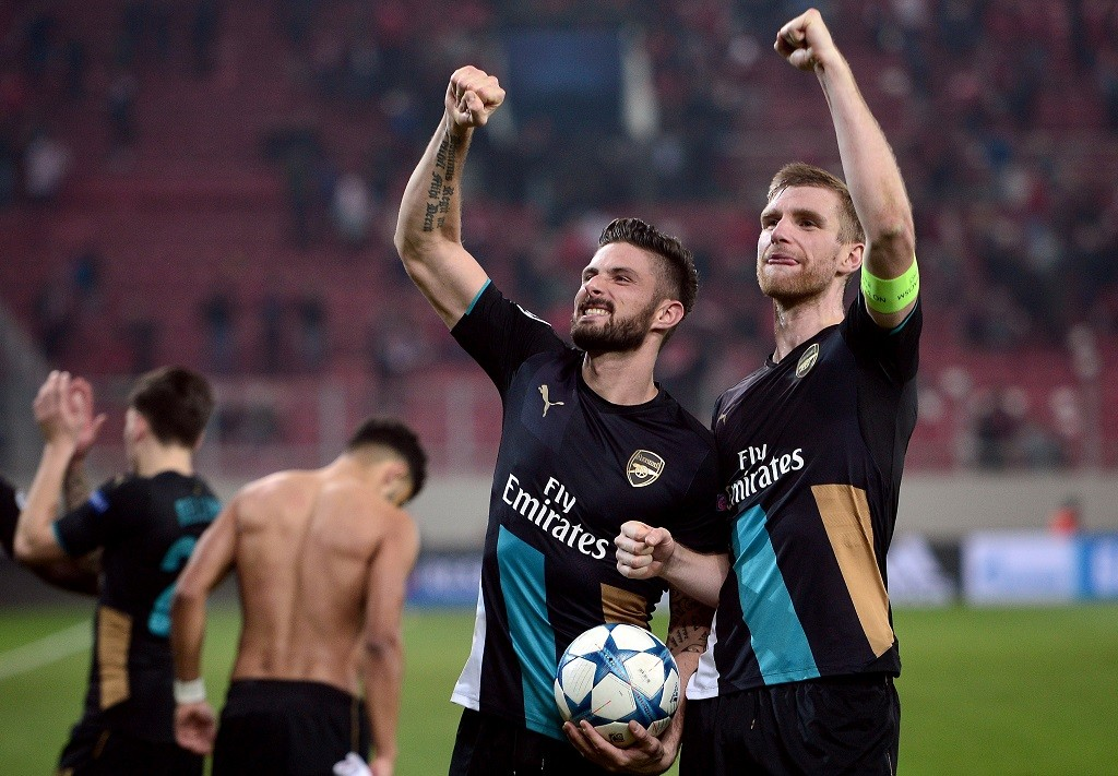 Arsenal's French forward Olivier Giroud (L)and Arsenal's German defender Per Mertesacker celebrate after the UEFA Champions League Group F football match between Olympiacos and Arsenal at the Georgios Karaiskakis Stadium in Piraeus near Athens on December 9, 2015.  Arsenal won the match 0-3. / AFP / LOUISA GOULIAMAKI