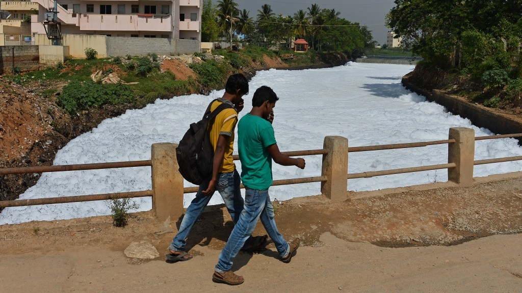 Indian pedestrians cover their noses as they cross a bridge over a frothing canal, which once carried water from Bellandur Lake to Varthur Lake, in east Bangalore on May 1, 2015. The innocuous-looking foam, which from a distance, looks like snow is nothing but toxic effluent caused by the polluted sewage water overflowing from nearby Bellandur Lake. The foam is a result of the water in the lake having high content of ammonia and phosphate and very low dissolved oxygen. Sewage from many parts of the Bangalore is released into lakes, leaving it extremely polluted. The foam during heavy rains spill onto the road, causing a traffic pile besides spreading unbearable stench in the air in the neighbourhood. AFP PHOTO/Manjunath KIRAN / AFP / MANJUNATH KIRAN
