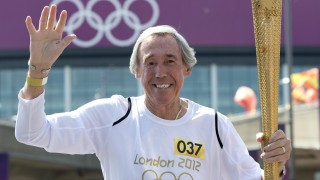 England legend goalkeeper Gordon Banks carries the Olympic Torch in front of Wembley Stadium in west London on July 25, 2012 two days before the start of the London 2012 Olympic Games.  AFP PHOTO / MIGUEL MEDINA / AFP / MIGUEL MEDINA