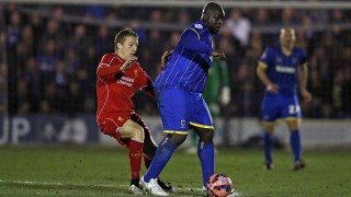 """AFC Wimbledon's English striker Adebayo Akinfenwa vies with Liverpool's Brazilian midfielder Lucas Leiva (L) during the English FA Cup third round football match between AFC Wimbledon and Liverpool at The Cherry Red Records Stadium in Kingston Upon Thames, south west London on January 5, 2015. AFP PHOTO / ADRIAN DENNIS  RESTRICTED TO EDITORIAL USE. No use with unauthorized audio, video, data, fixture lists, club/league logos or """"live"""" services. Online in-match use limited to 45 images, no video emulation. No use in betting, games or single club/league/player publications. / AFP / ADRIAN DENNIS"""
