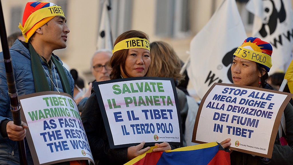 People hold placard to highlight environmental issues in Tibet during a rally calling for action on climate change on November 29, 2015 in Rome a day before the launch of the COP21 conference in Paris. Some 150 leaders including US President Barack Obama, China's Xi Jinping, India's Narendra Modi and Russia's Vladimir Putin will attend the start of the UN conference Monday, tasked with reaching the first truly universal climate pact. The goal is to limit average global warming to two degrees Celsius (3.6 degrees Fahrenheit), perhaps less, over pre-Industrial Revolution levels by curbing fossil fuel emissions blamed for climate change.  AFP PHOTO / TIZIANA FABI / AFP / TIZIANA FABI