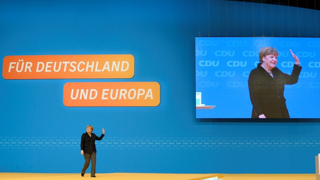 German Chancellor and Christian Democratic Union (CDU) leader Angela Merkel waves to the delegates after her speech at the CDU annual federal congress in Karlsruhe, southern Germany, on December 14, 2015. German Chancellor Angela Merkel is seeking to stamp out dissent in her conservative Christian Democratic Union's party congress over a record refugee influx after months of corrosive infighting.  AFP PHOTO / THOMAS KIENZLE / AFP / THOMAS KIENZLE