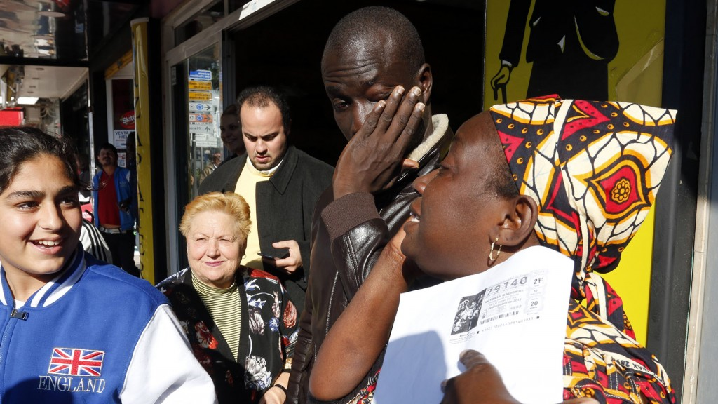 """Senegalese Ngame (2nd R) wipes his eyes next to a woma who holds a photocopy of a winning lottery ticket of the Spanish Christmas' lottery draw on December 22, 2015 in the southeastern town of Roquetas de Mar. An unemployed Senegalese man named Ngame who was rescued by the Spanish coastguard after making a risky journey from Morocco eight years ago on a packed wooden boat, won 400,000 euros ($437,000) as he was one of the holders of one of the 1,600 tickets with the winning number -- 79140 -- in December 22 Spain's annual Christmas lottery draw, known as """"El Gordo"""" (The Fat One), newspaper La Voz de Almeria reported on December 23, 2015. AFP PHOTO / AFP / STRINGER"""