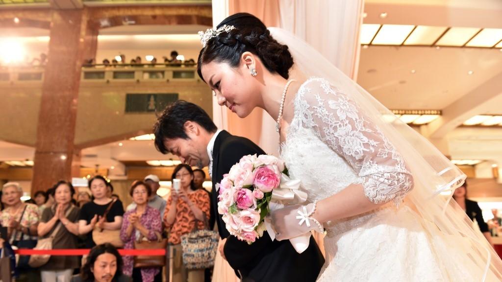 Bride Rie Oka (R) and her father Kazuyoshi Oka (L) arrive for a wedding ceremony at the Mitsukoshi department store in Tokyo on August 8, 2015. Mitsukoshi and bridal service company Minnano-wedding produced a non-religious wedding ceremony before some 500 shoppers at the department store.  AFP PHOTO / Yoshikazu TSUNO / AFP / YOSHIKAZU TSUNO