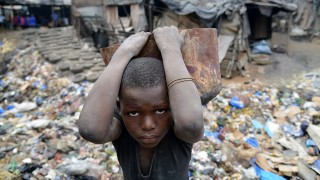 A child works in a forge in Abidjan, Ivory Coast on July 29, 2015. School attendance is 'mandatory' for children aged 6 to 16 from the beginning of the next school term 2015/2016 - a measure based on a recent decision by President Alassane Ouattara. AFP PHOTO / ISSOUF SANOGO / AFP / ISSOUF SANOGO