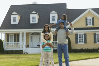 Young couple standing with their children in front of a house